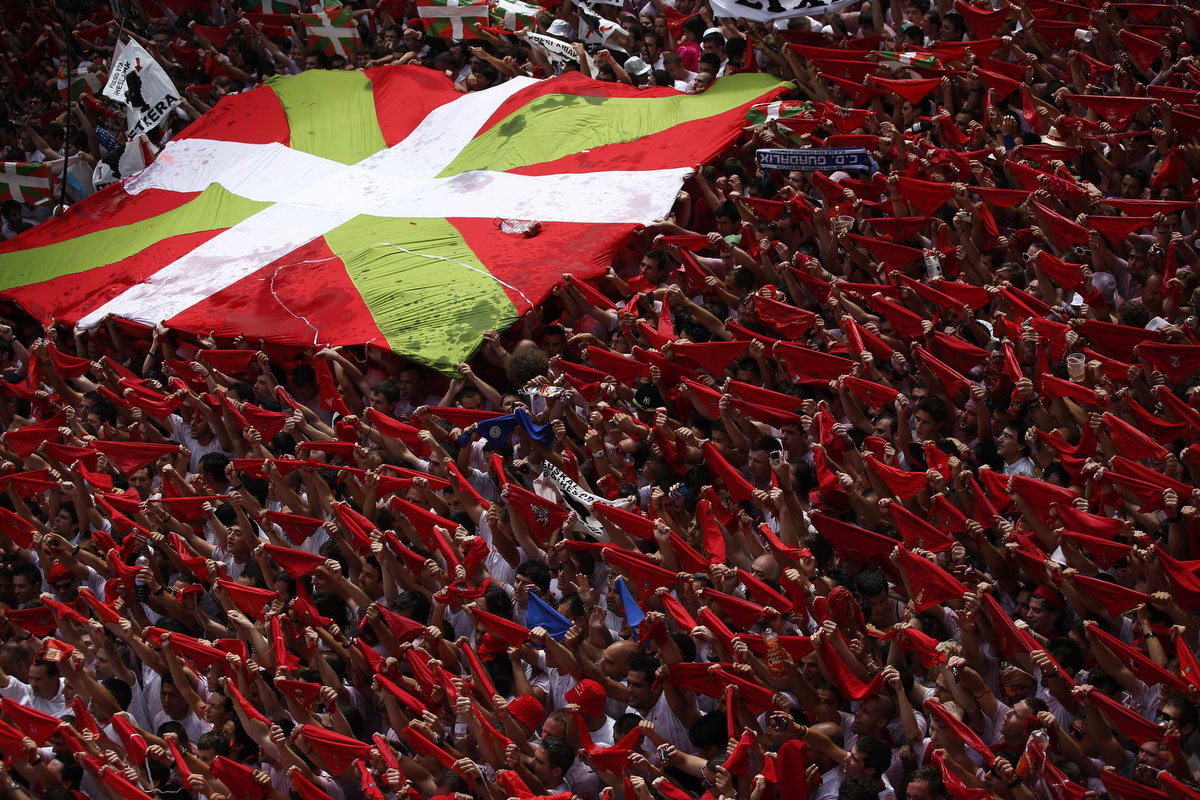 "Revellers hold up their red scarves next to a Basque Country flag during the start of the San Fermin Festival in Pamplona July 6, 2012. The annual festival, best known for its daily running of the bulls, kicked off on Friday with the traditional ""Chupinazo"" rocket launch and will run until July 14. (Susana Vera/Reuters photo)"